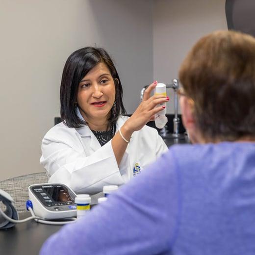 Professor Sharrel Pinto shows a client how to use an inhaler