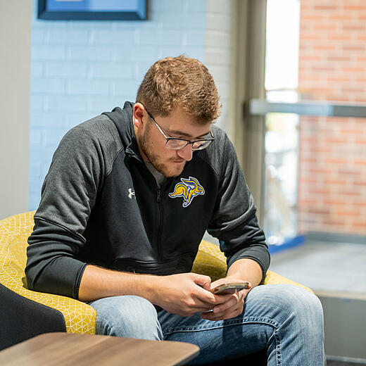 Student with cell phone in his hands