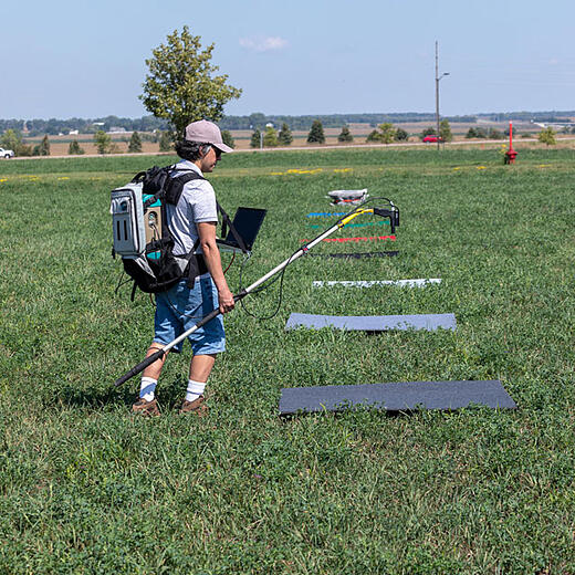 Research assistant Pedro Oliveira holding ASD Fiel Spec over colored squares in alfalfa field