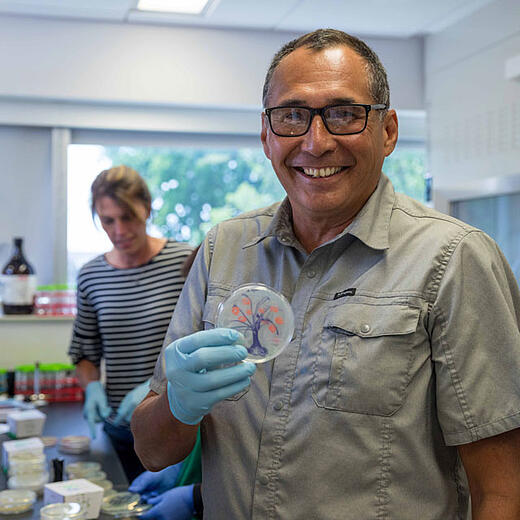 Teacher Brian LaBelle holds a petri dish with a tree he painted using bacteria