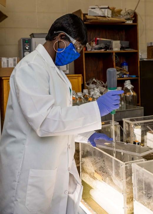 Augustine taking sample from photobioreactor