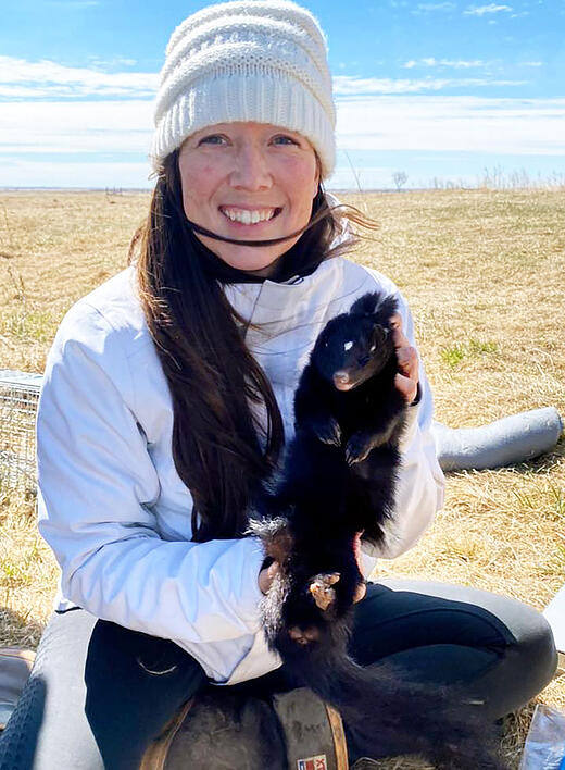 Kara White holds a civet cat trapped before the pandemic