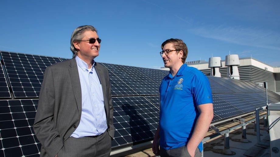 Reinaldo Tonkoski, left, and Tim Hansen standing in front of solar panels atop Daktronics Hall