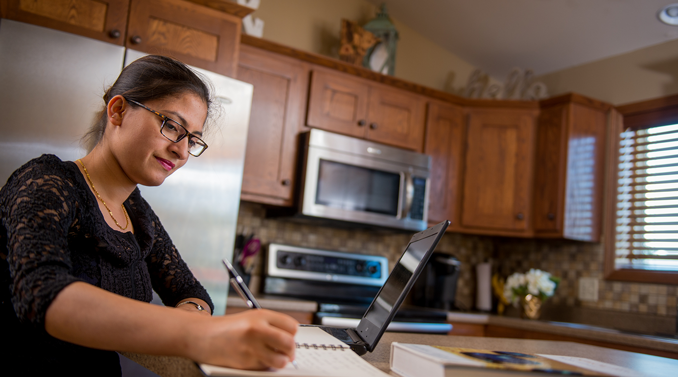 female student completing online classes in her kitchen